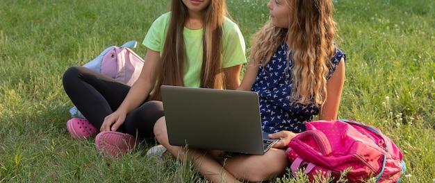 Twee meisjes met laptop en aktetassen die huiswerk maken of plezier hebben terwijl ze buiten op het gras zitten