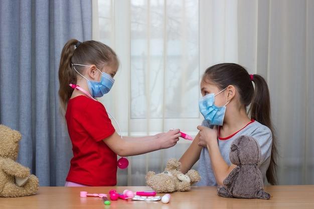 Twee meisjes met medische maskers spelen in het ziekenhuis met speelgoed waarvan het jongste meisje wordt gevaccineerd