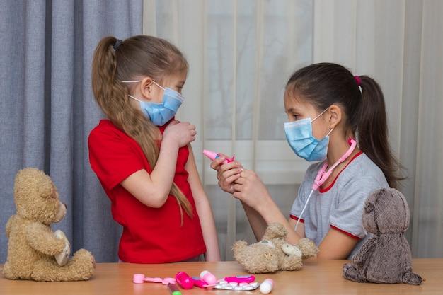 Twee meisjes met medische maskers spelen met speelgoed in het ziekenhuis, het jongste meisje dat wordt gevaccineerd