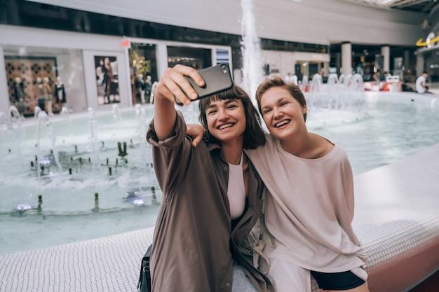 Twee meisjes nemen een selfie in het winkelcentrum, naast een fontein
