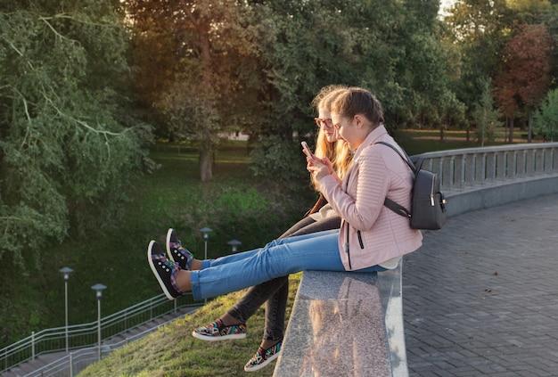 Twee meisjes nemen foto van hun voeten aan de telefoon