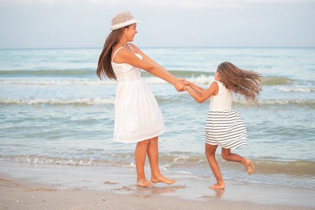 Twee meisjes ontspannen op het strand en wandelen de golven van de zee op een zonnige zomeravond tijdens vakantie