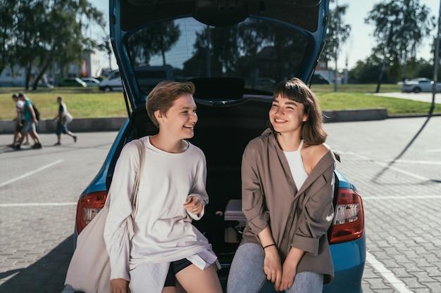 Twee meisjes op de parkeerplaats bij de open kofferbak poseren