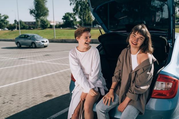 Twee meisjes op de parkeerplaats bij de open kofferbak