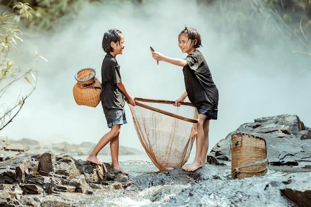 Twee meisjes op het platteland van thailand vissen vangen in de stroom