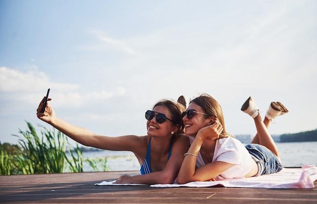 Twee meisjes op het strand liggen op de grond en genieten van warm zonlicht.