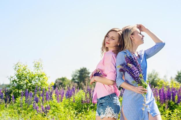 Twee meisjes op het veld met lupines