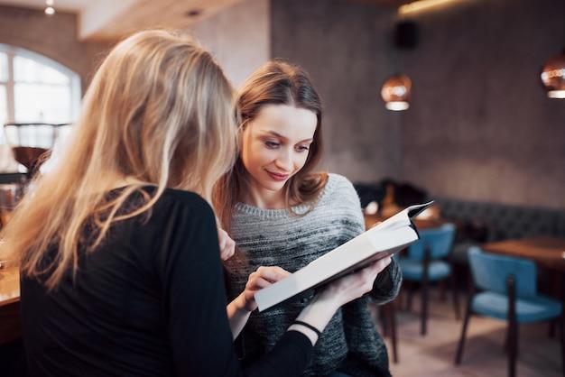 Twee meisjes opgenomen in het lezen van boek tijdens de pauze in het cafe. leuke mooie jonge vrouwen lezen boek en drinken koffie