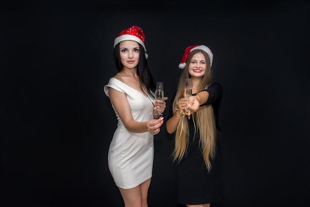 Twee meisjes poseren met champagne en bengaalse lichten