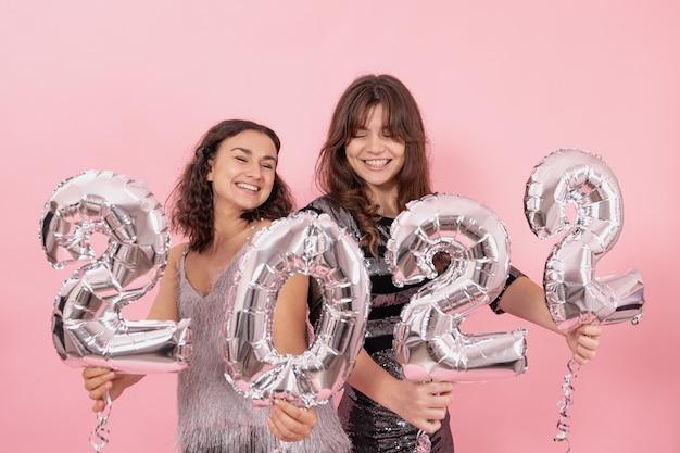 Twee meisjes poseren tegen een roze achtergrond en houden in hun handen zilveren ballonnen met nummers 2022.