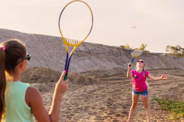Twee meisjes spelen badminton buiten