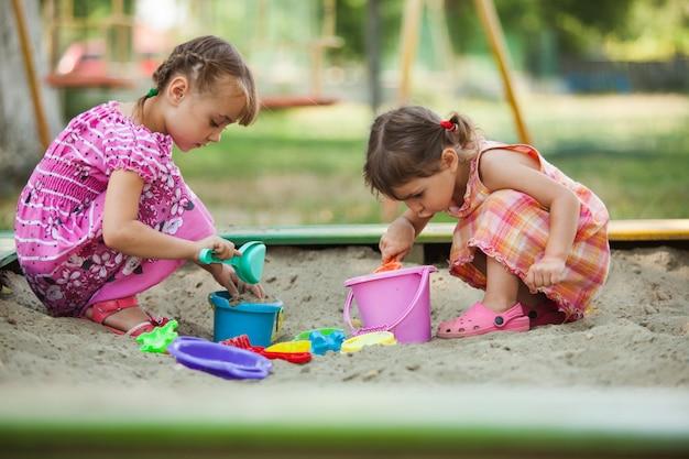 Twee meisjes spelen in de zandbak