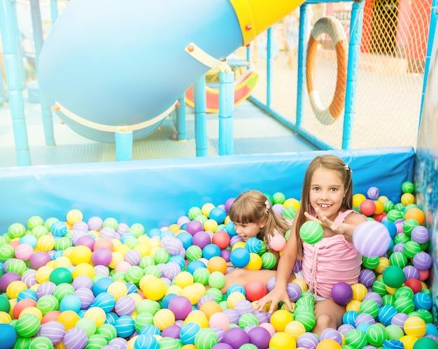 Twee meisjes spelen in het zwembad met plastic ballen