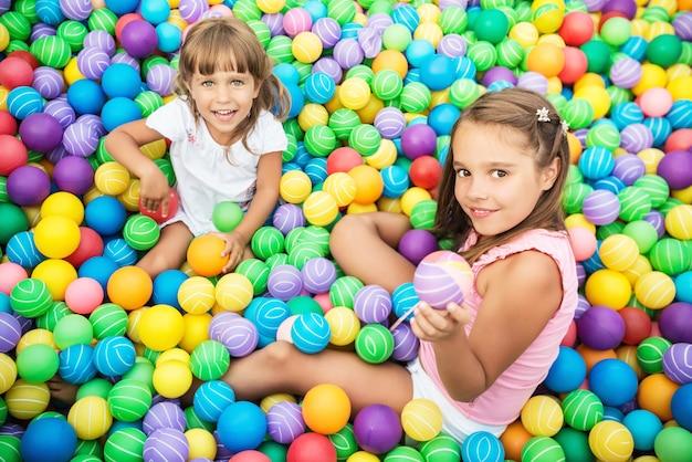 Twee meisjes spelen in zwembad met plastic ballen