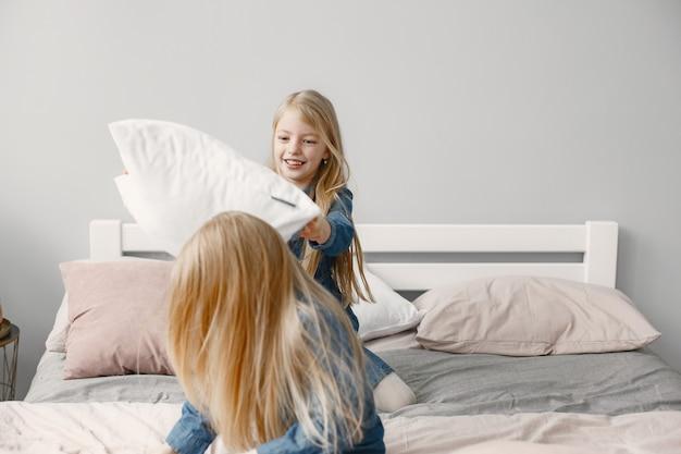 Twee meisjes spelen met kussens in de slaapkamer. slaapkamer feest.