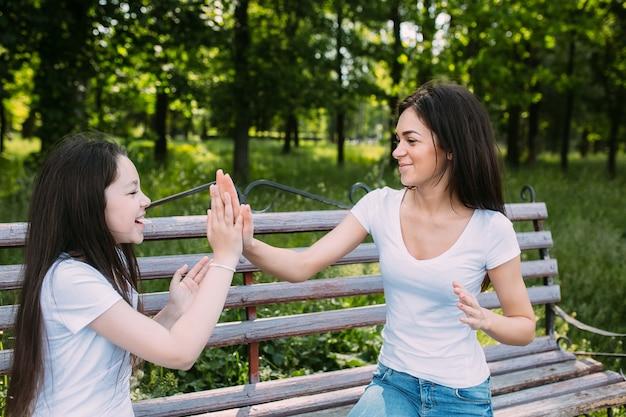 Twee meisjes spelen patty-cake in het park