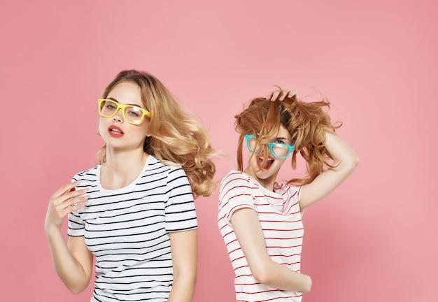Twee meisjes staan naast elkaar in gestreepte tshirts vriendschap roze achtergrondmode background