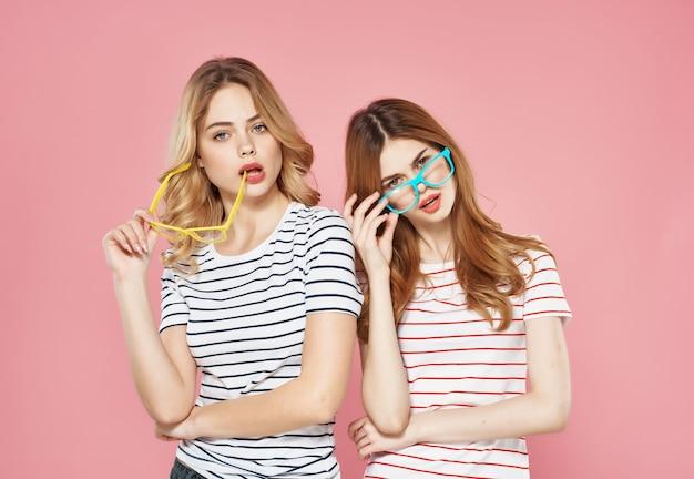 Twee meisjes staan naast elkaar in gestreepte tshirts vriendschap roze achtergrondmode