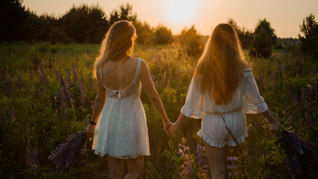 Twee meisjes staan op het veld met boeketten van paarse bloemen