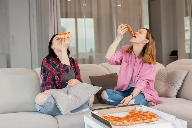 Twee meisjes stoppen vrolijk stukjes pizza in hun mond terwijl ze lachend thuis op de beige bank zitten hoge kwaliteit foto