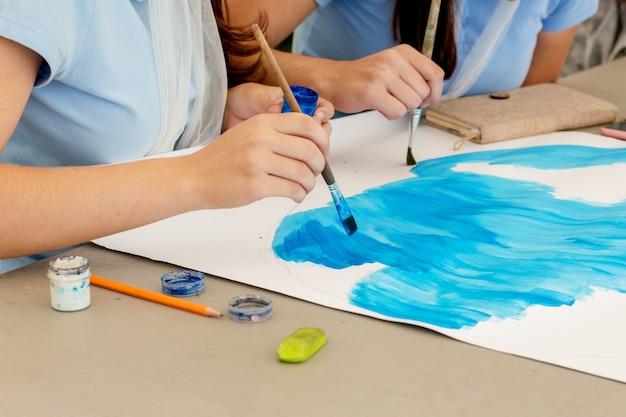 Twee meisjes tekenen samen een tekening op papier. een penseel op papier tekenen