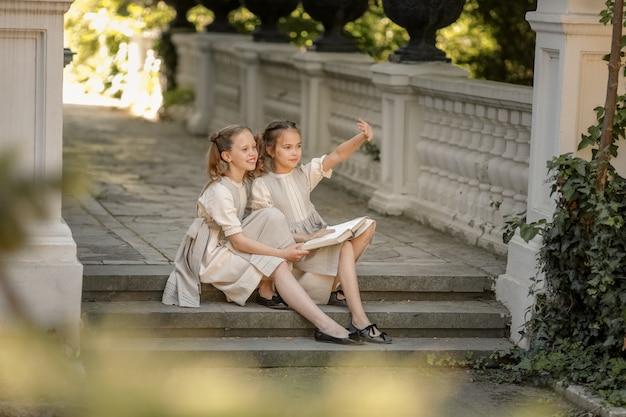 Twee meisjes van basisschoolmeisjes lezen een boek op de binnenplaats van de academie.