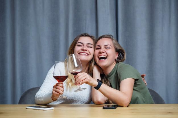 Twee meisjes van europees uiterlijk met blond haar zitten aan tafel, drinken wijn en lachen, ontspannen thuis, alcohol