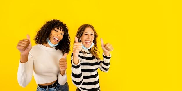 Twee meisjes van gemengd ras die met omhoog duimen en blauw medisch masker knipogen die positief denken tegen pandemie van het coronavirus die op gele muurkopieruimte wordt geïsoleerd. glimlachende zelfverzekerde duizendjarige vrouwenvrienden