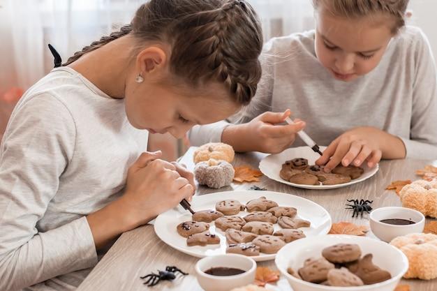 Twee meisjes versieren halloween-peperkoekkoekjes op borden met chocoladesuikerglazuur. kooktraktaties voor halloween-feest. levensstijl