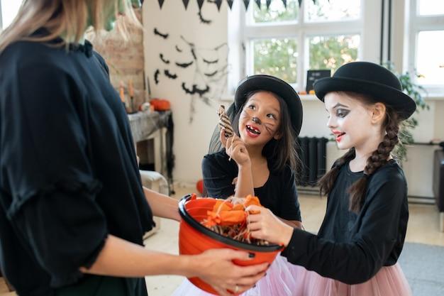 Twee meisjes vragen jonge vrouw in zwarte kleding om halloween-traktaties