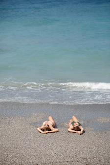 Twee meisjes vriendin zitten op de zanderige kust van de zee en de golven doordrenkt hen in badpakken op een zonnige warme dag