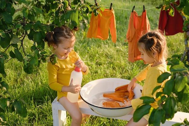 Twee meisjes wassen kleren in een kom die onder een boom in de tuin zit