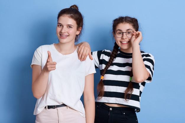 Twee meisjes zien er gelukkig uit, wijzen en kijken met een positieve uitdrukking, dames staan in stijlvolle kledij geïsoleerd.