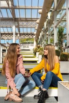 Twee meisjes zitten graag op de trap van een stadskas omringd door cactussen