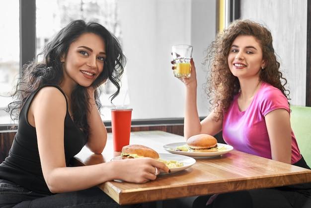 Twee meisjes zitten in café in de buurt van venster, het eten van fast food.