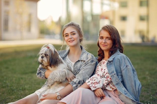 Twee meisjes zitten in een park met een kleine hond