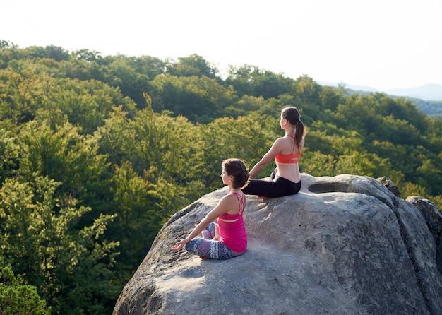 Twee meisjes zitten in lotus houding op enorme rotsen