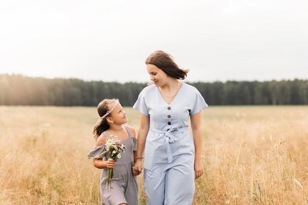 Twee meisjes zusjes lopen door de wei met een bos bloemen
