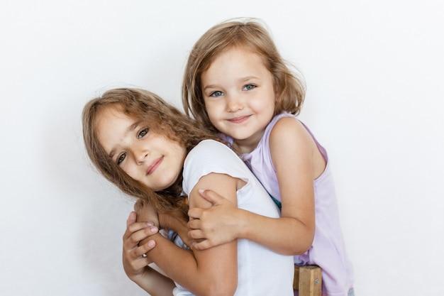 Twee meisjes, zussen, elkaar omhelzen, relaties, communicatie, familie, steun en vreugde, emoties, baby, ruzies