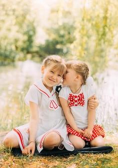 Twee meisjes zussen knuffelen en hebben plezier in de zomer in de natuur. concept van gelukkige jeugd en zomer vrije tijd. kinderen spelen buiten. verticaal
