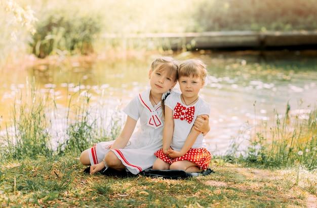 Twee meisjes zussen knuffelen en hebben plezier in de zomer in de natuur. concept van gelukkige jeugd en zomer vrije tijd. kinderen spelen buiten.