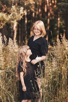 Twee meisjes zussen knuffelen in de natuur in de zomer