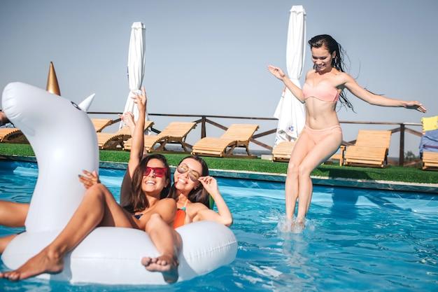 Twee meisjes zwemmen op witte vlotter. ze killen en hebben rust. derde springt in het water. ze kijkt naar beneden. andere twee modellen poseren voor de camera.