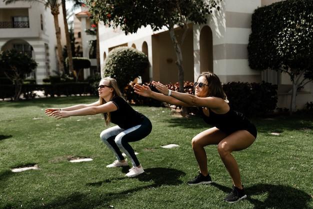 Twee meisjesatleten strekken zich uit over het gazon bij het huis