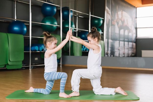 Twee meisjeskind die samen bij gymnastiek uitoefenen