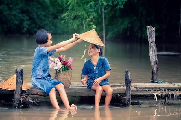 Twee meisjeskinderen die en samen water op houten brug over moeras zitten spelen