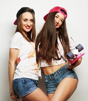 Twee meisjesschaatsers worden gek en hebben samen plezier. mooie sportieve vrouwen, positieve emotie. grijze achtergrond.