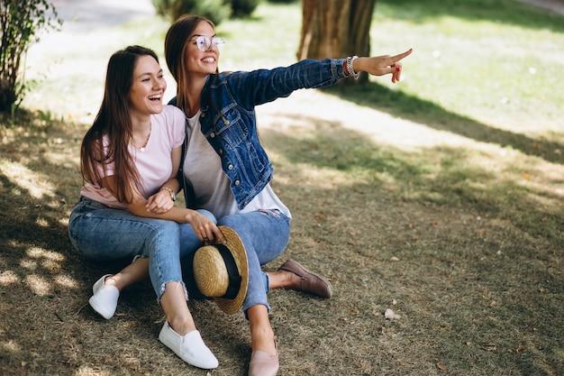 Twee meisjesvrienden die in park zitten