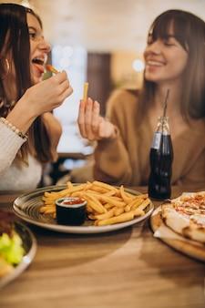 Twee meisjesvrienden die pizza in een koffie eten