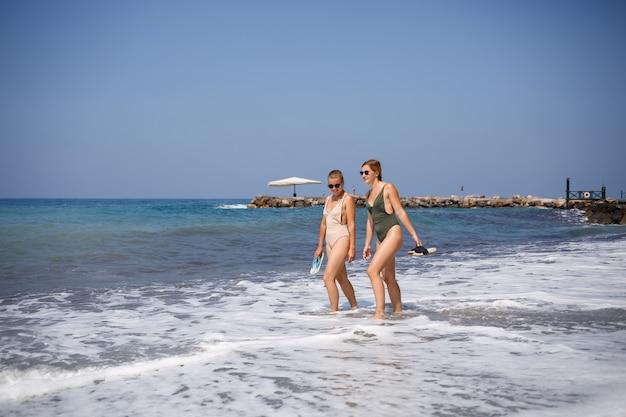 Twee meisjesvrienden lopen langs de zeezandkust in zwemkleding op een zonnige warme dag